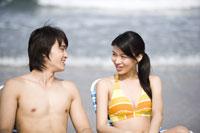 couple sitting in deckchairs on beach