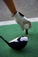 Man placing golf ball on tee