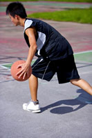 boy dribbling basketball outdoors