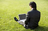 businessman sitting on grass with laptop 11010010642| 写真素材・ストックフォト・画像・イラスト素材|アマナイメージズ