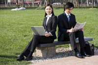 businesspeople sitting on bench by park