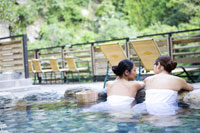 women with towel bathing in hot spring