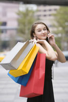 girl on the phone holding shopping bags