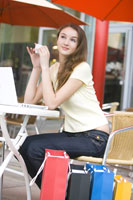 Teenage girl at cafe, with shopping bags
