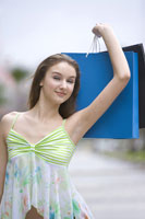 Teenage girl holding up shopping bags