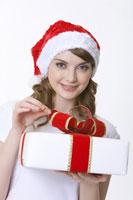 girl wearing santa hat holding gift