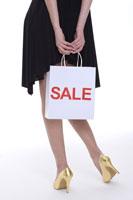girl holding shopping bag behind back