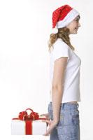 girl wearing Santa hat holding gift box