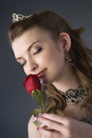 girl holding a rose with eyes closed