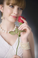 girl wearing jewelries holding rose