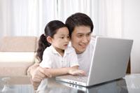 Father teaching daughter using laptop