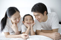 Family with daughter lying on bed