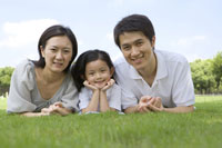Family with daughter lying on lawn