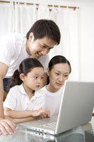 Family with daughter using laptop