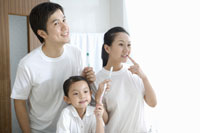 Family with daughter holding toothbrush