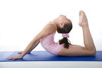 Girl practicing gymnastic pose on pad