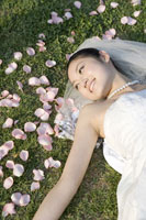 Young bride lying on lawn with petals