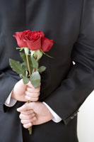 Young groom holding flowers behind back