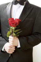 Young groom holding roses