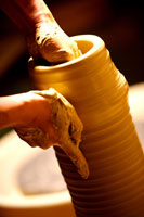 Hands of potter at work throwing pot