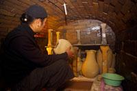 Potter sitting in ceramic kiln