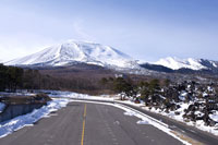 Empty road and snowcapped mountain