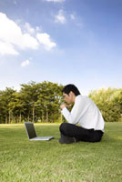 A business man sitting on lawn and looking at the laptop