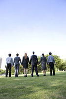 Six business people standing on the lawn,hand in hand