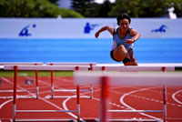 Female athlete jumping hurdles,front view