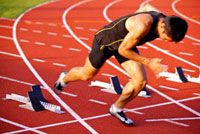 Male athlete running from track starting block