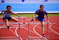 Two female athletes jumping hurdles,front view