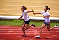Two female athletes passing relay baton