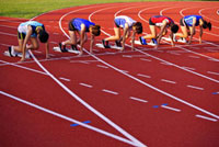 Five female athletes in starting positions on running track
