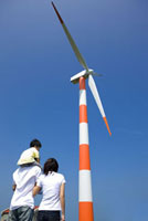 Young family with one child looking at a wind turbine