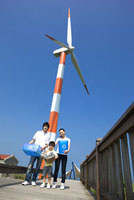 Young family with recycled stuffs before a wind turbine