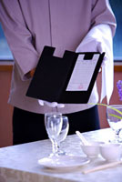 Waiter standing near the table and showing the bill