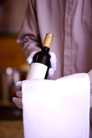 Close-up of hands holding a bottle of wine and a towel