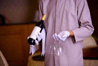 Young waiter holding a bottle of red wine and wine glasses