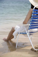 Young woman sitting on beach chair with feet in water