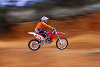 Young man motocross over field