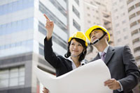 Businessman and businesswoman looking away with helmets