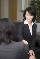 Businesswomen shaking hands together and having interview