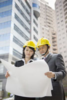 Businessman and businesswoman holding blueprint together