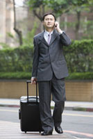 Businessman holding a suitcase and on the phone