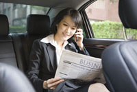 Businesswoman reading newspaper and on the phone in the car