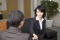 Businesswoman and businessman shaking hands together