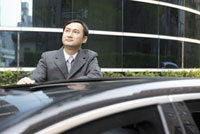 Businessman standing with vehicle and looking up 11010042772| 写真素材・ストックフォト・画像・イラスト素材|アマナイメージズ