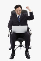 Businessman sitting on chair & using laptop with one fist up