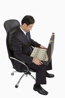 Businessman sitting on chair and holding a suitcase