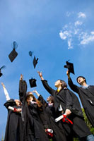Young college students throwing mortar board into mid-air